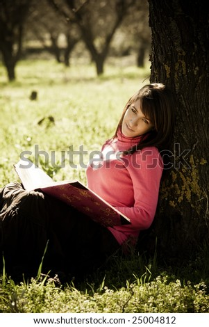 Young cheerful woman enjoying a book in the forest.