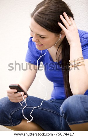 Young cheerful woman reading book and listening to music - stock photo