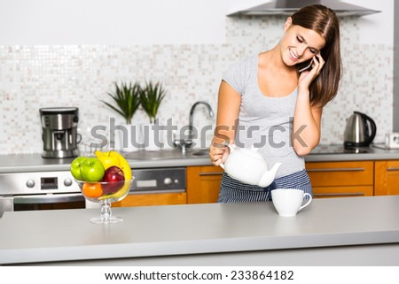 Young cheerful woman talking on the phone in kitchen - stock photo