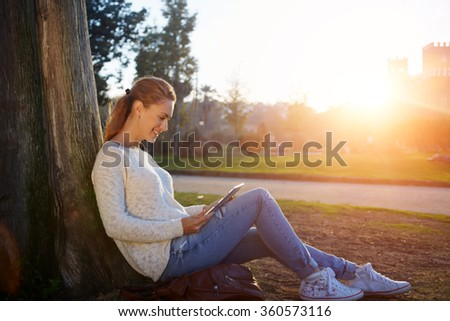 Young cheerful woman watching funny video or reading electronic book on touch pad while resting outdoors, happy smiling female student using digital tablet for studying while sitting in the park - stock photo
