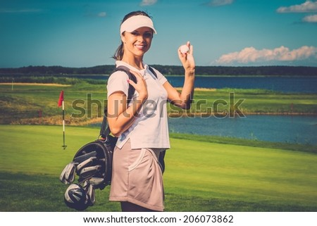 Young cheerful woman with bag and ball on a golf field - stock photo