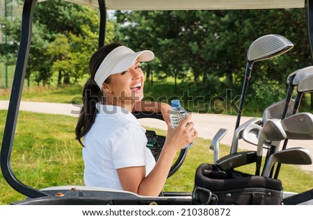 Young cheerful woman with bottle of water driving golf cart  - stock photo