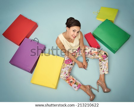 Young cheerful woman with colored paper shopping bags. Shopaholic. Shopping concept and ideas. Urban lifestyle. Image toned. - stock photo