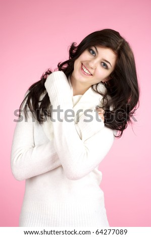 Young cheerful woman with white sweater over pink background - stock photo
