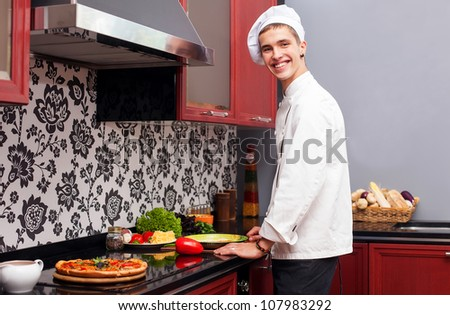 Young chef cooks in the kitchen smiling
