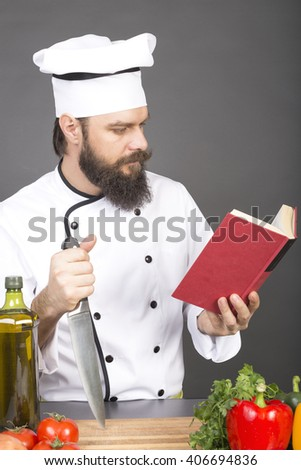Young chef in uniform reading a recipe, ready to cook, over gray background - stock photo