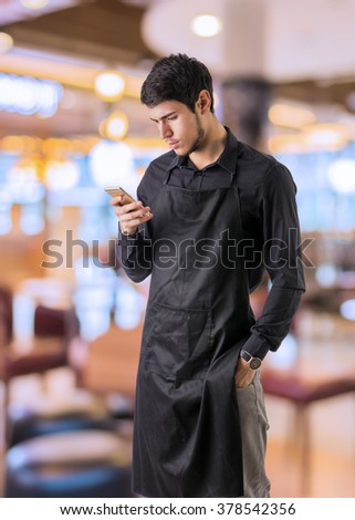 Young chef or waiter posing, wearing black apron and white shirt, using cell phone or smartphone or device for orders, in bar, restaurant or diner - stock photo