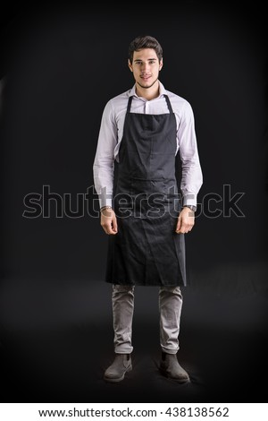 Young chef or waiter wearing black apron  - stock photo
