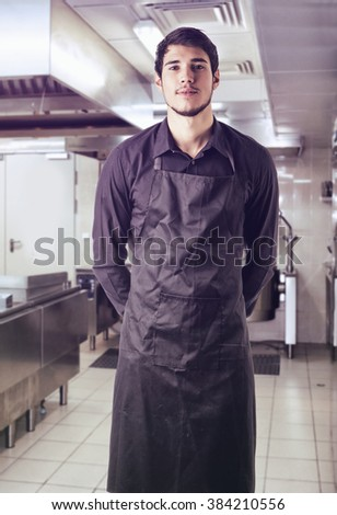 Young chef or waiter wearing black apron isolated - stock photo