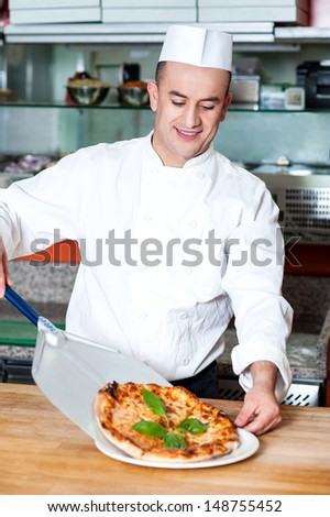 Young chef placing pizza carefully on plate - stock photo