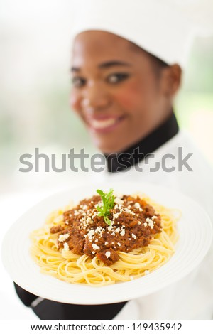 young chef presenting delicious spaghetti dish - stock photo