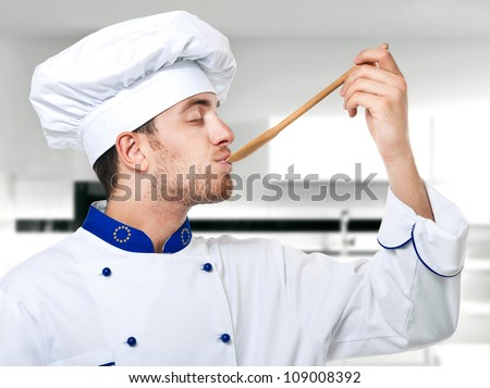 Young chef tasting food - stock photo