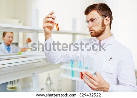 Young chemist analyzing new substance in lab on background of his assistant - stock photo