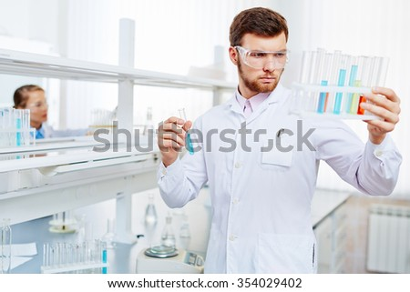 Young chemist looking at flasks with liquid chemical substances - stock photo