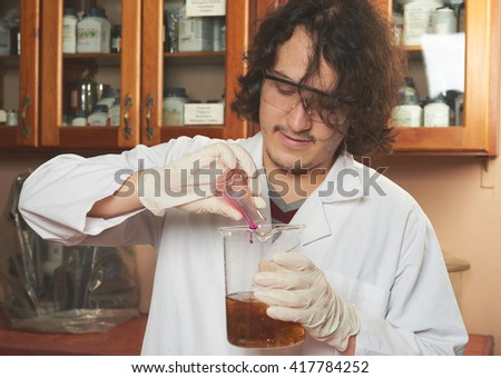 young chemist make experiment in lab - stock photo