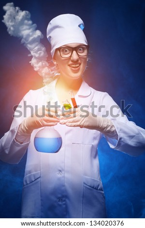 young chemist makes the experience of with the smoke. studio shot - stock photo