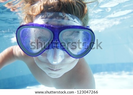 young child diving underwater in mask in pool - stock photo