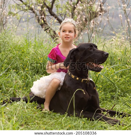 Young child girl dressing up in fancy dress in a green nature field, sitting on her great dane dogs back being thoughtful. Happy dog owner playing with her pet and enjoying a summer holiday together. - stock photo