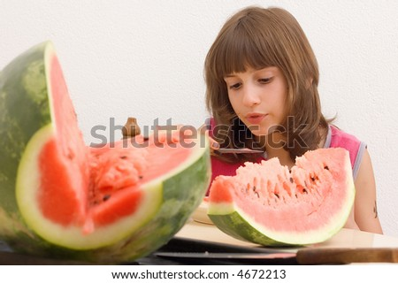 Young child girl eating watermelon in the kitchen