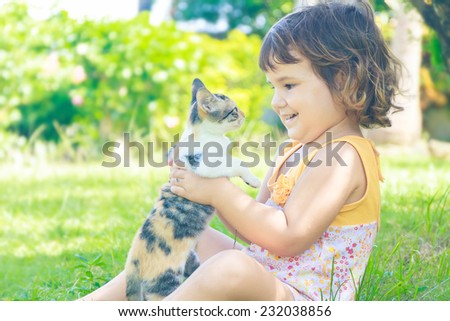 young child girl having fun with cat, little kitten on natural background - stock photo