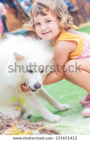 young child girl having fun with white dog on natural background - stock photo