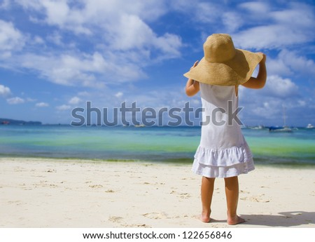 young child girl in summer hat on tropical sea background - stock photo