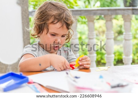 young child girl writing in notebook, outdoors portrait, education idea - stock photo