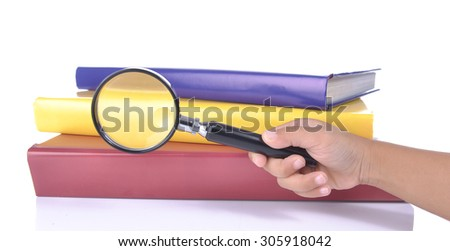 young child hand hold a magnifying glass looking at books. room for text. Symbol of knowledge and science - stock photo