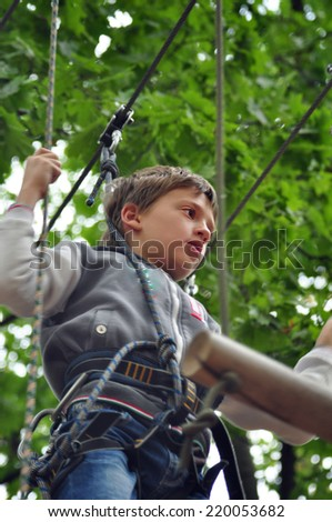 Young child having fun  in a climbing adventure activity park - stock photo