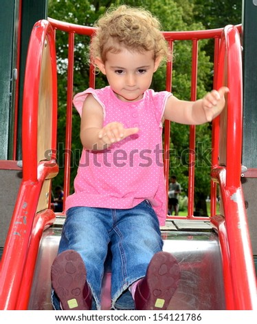 Young child having fun on a slide at the park. Toddler girl with blonde curly hair, wearing pink top and blue jeans.