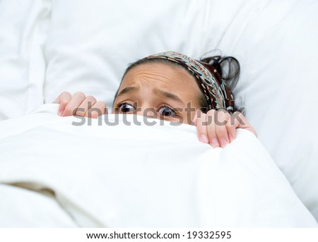 Young child hiding behind blanket while watching scary story - stock photo