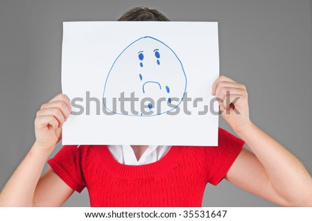 Young child holding up sign to mask true emotion - psychology concept
