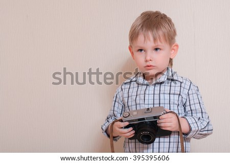 young child holding vintage camera