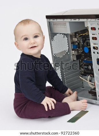 young child in blue shirt with open computer on neutral background