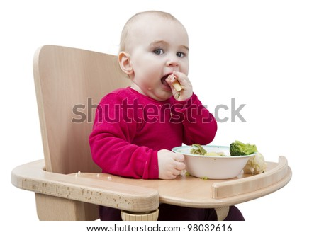 young child in red shirt eating vegetables in wooden chair.