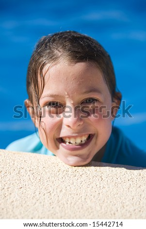 Young Child in Swimming Pool Smiling - stock photo