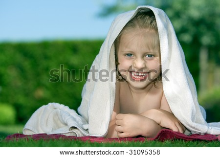 Young child is lying on lawn with towel on head - stock photo
