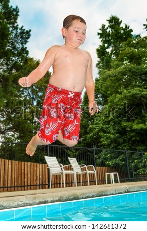Young child jumping into pool from side - stock photo