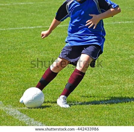 Young child kicks the ball