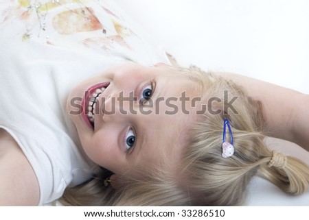 Young child lies smiling on the floor - stock photo