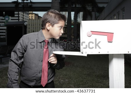 Young child looking in a mailbox - stock photo