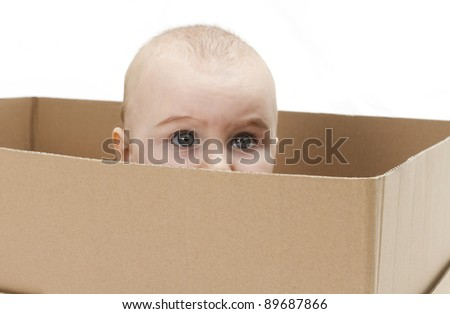 young child looking out of open cardboard box