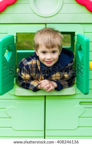young child looks out of the window of the plastic house, playground - stock photo
