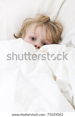 Young child, lying awake in his bed, with his eyes wide open, covering himself up, scared from the nightmare he just had - stock photo