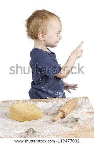 young child making cookies pointing at side - stock photo