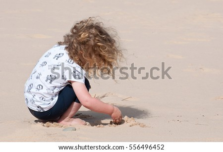 Young child on a sandy beach exploring and having fun