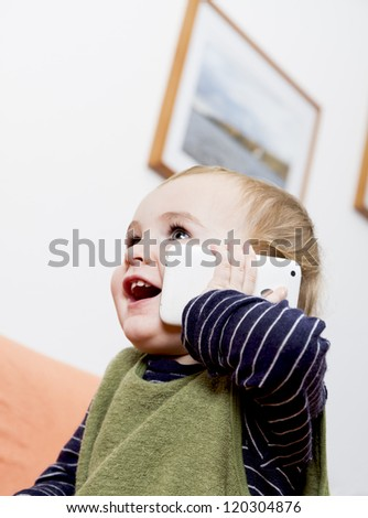 young child on couch with white cell phone - stock photo