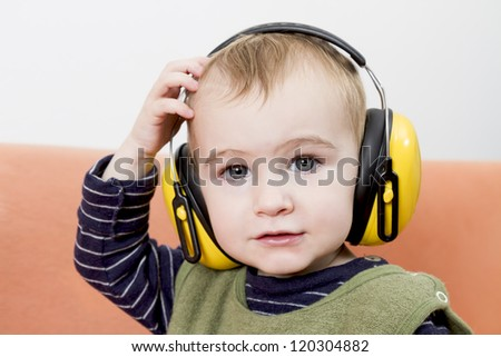 young child on couch with yellow earmuffs - stock photo