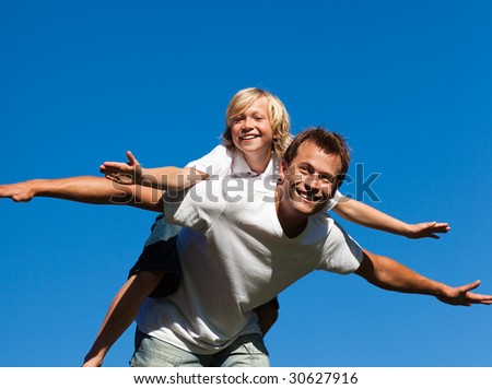 Young Child on his father's back - stock photo