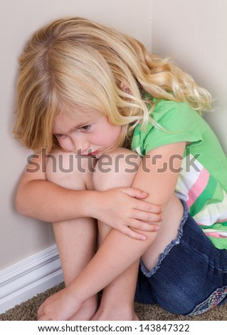 Young child or preschooler sitting in corner, with a sad look on face - stock photo